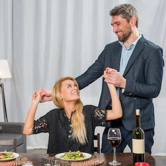Happy man holding hands of cheerful woman at table