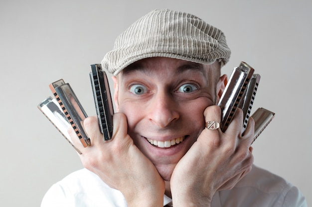 Happy man holding harmonicas
