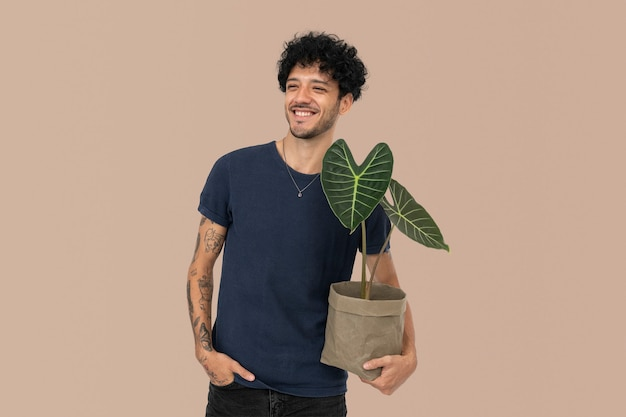 Happy man holding houseplant in sustainable packaging