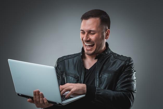 Счастливый человек, держащий ноутбук на сером фоне