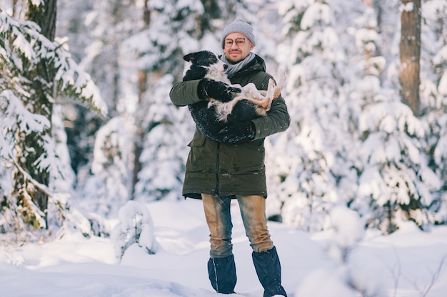 Happy man holding lovely dog in his hands in snowy forest. smiling boy hugging adorable puppy in winter wood. pet lover.  dog - human`s friend concept.