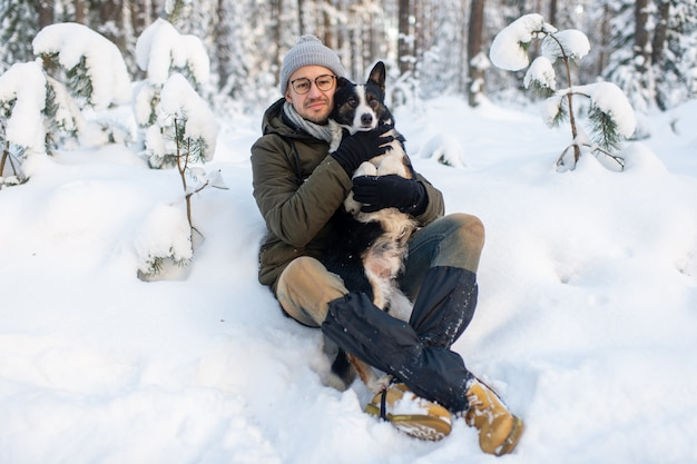 Happy man holding lovely dog in his hands in snowy forest. smiling boy hugging adorable puppy in winter wood. pet lover.