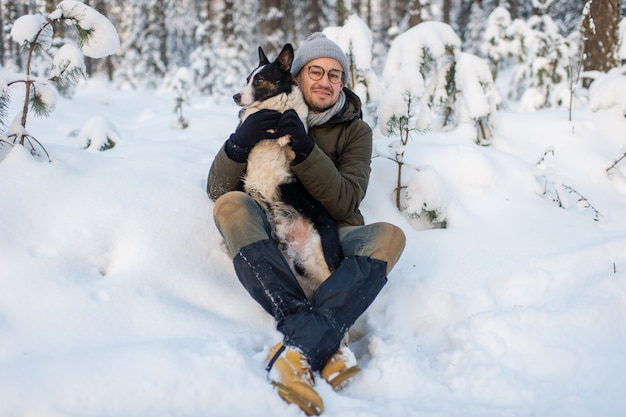 Happy man holding lovely dog in his hands in snowy forest.