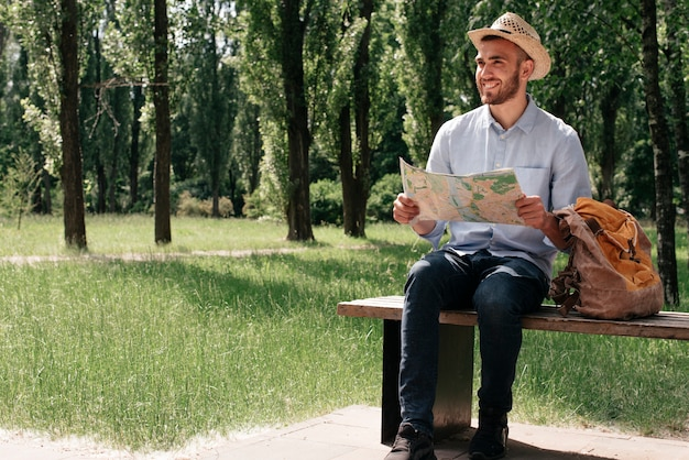 Happy man holding map sitting on bench with backpack