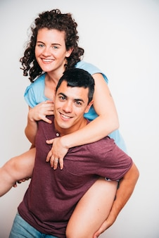 Happy man holding on back young woman