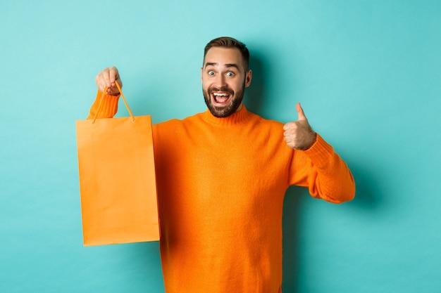 오렌지 쇼핑 가방을 들고 할인에서 기쁨과 축하, 엄지 손가락을 표시하고 추천, 파란색 배경 위에 서 행복 한 사람.