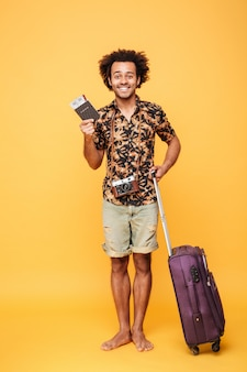Happy man holding passport and suitcase.