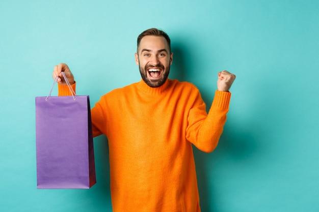 Счастливый человек, держащий фиолетовую сумку для покупок и радуясь, получил скидку и праздновал, стоя на бирюзовом фоне.