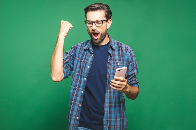 Happy man holding smartphone and celebrating his success over green background.