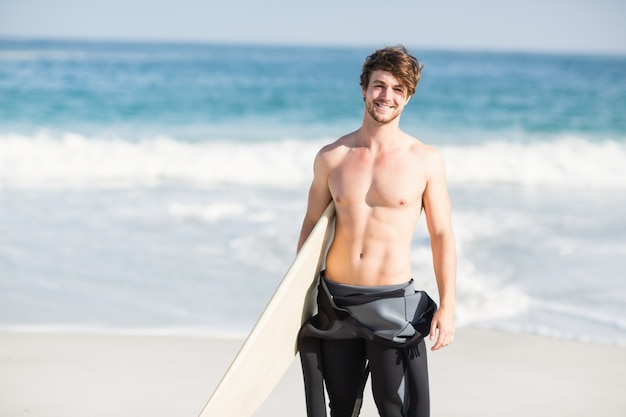 Happy man holding a surfboard on the beach