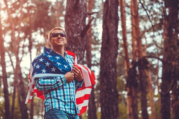 夕暮れ時の公園で米国旗を持って幸せな男