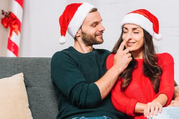 Счастливый человек держит нос женщины на диване
