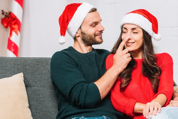 Happy man holding woman's nose on sofa