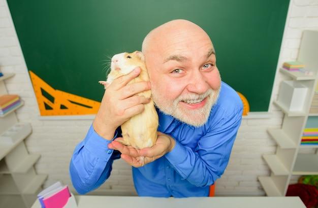 幸せな男は手にモルモットを保持します動物学自然の概念所有者の笑顔で小さなモルモット