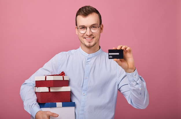 Happy man holds three colored gifts in boxes with lid and bow in his hands