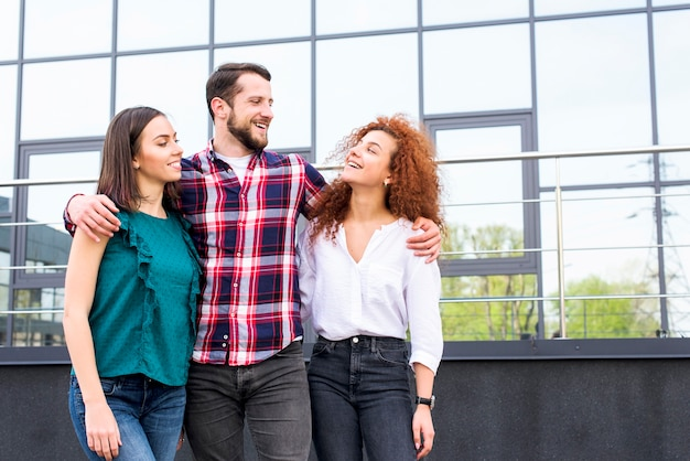 Happy man hugging his female friends standing in front of glass building