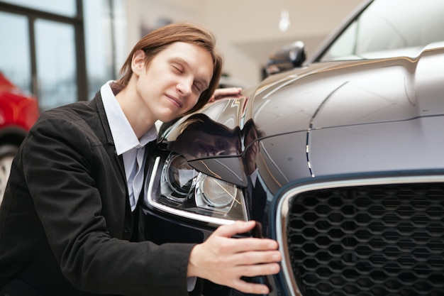 Happy man hugging his new automobile at dealership salon, copy space