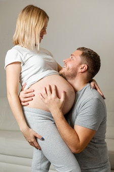 Happy man hugging pregnant woman at home