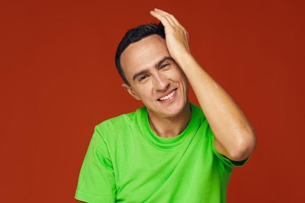 緑のtシャツを着た幸せな男は、赤い背景に彼の手で彼の頭に触れます