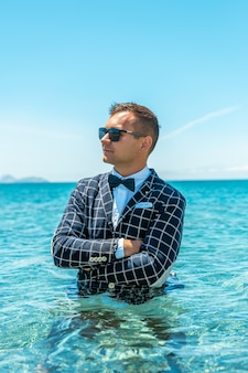 蝶ネクタイとスーツを着た幸せな男が海に立っています。
