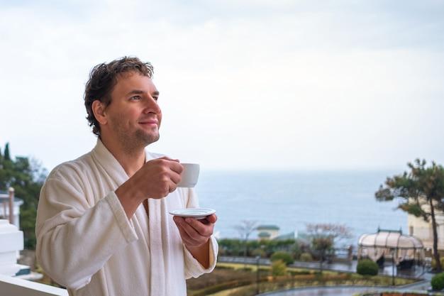 白いバスローブを着た幸せな男は、海の背景に朝のお茶やコーヒーを満たしています。休息、健康、目覚めの概念。