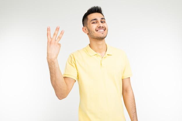 노란 셔츠에 행복 한 사람이 고립 된 흰색에 세 손가락을 보여줍니다