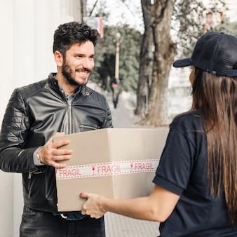 女性の宅配便から小包を受け取る黒いジャケットの幸せな男
