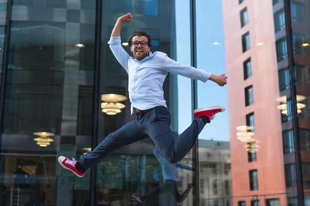 モダンな建物の近くでジャンプするカジュアルな服装で幸せな男