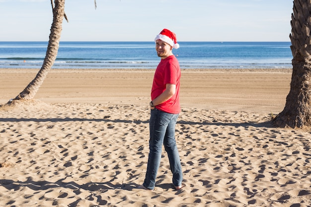 彼はビーチに立っている間、クリスマス帽子の幸せな男はあなたを見ています