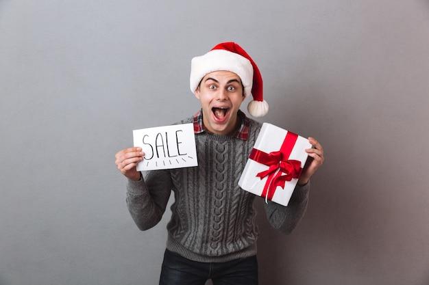 Счастливый человек в рождественской шапке санта-клауса с подарком