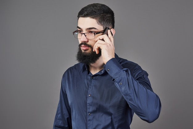 メガネで幸せな男は灰色の電話で話す