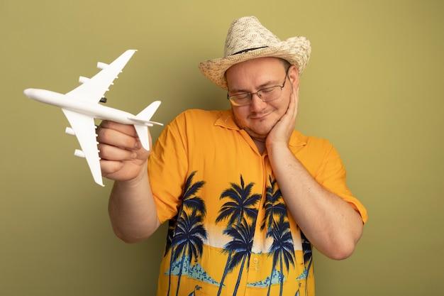 녹색 벽 위에 서있는 그의 뺨에 손으로 웃는 장난감 비행기를 들고 여름 모자에 주황색 셔츠를 입고 안경에 행복한 사람
