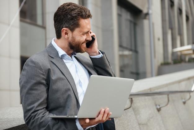 ビジネスセンターの近くに立っている間銀のラップトップに取り組んでいると携帯電話で話している灰色のスーツで幸せな男