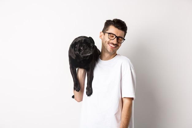 犬と恋に幸せな男、肩に子犬を保持し、笑顔、白い背景の上に立って