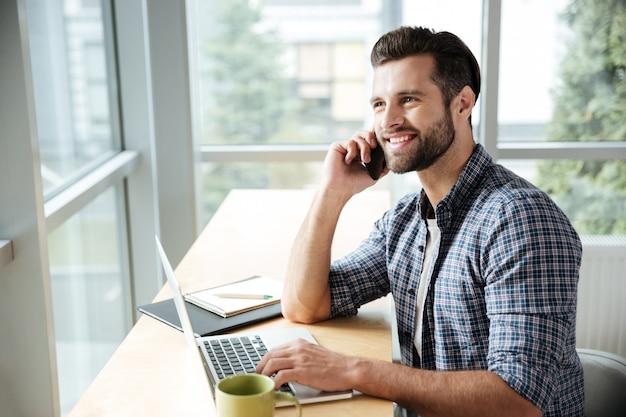 Счастливый человек в офисе коворкинг, разговор по телефону.