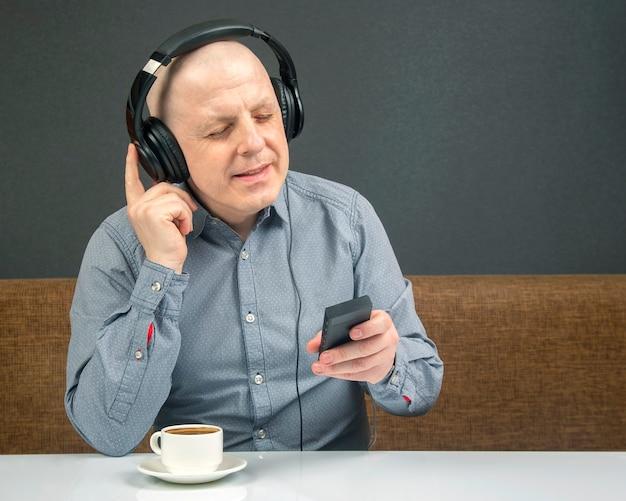 휴대용 풀 사이즈 헤드폰의 행복한 사람은 디지털 플레이어를 사용하여 음악을 듣습니다.