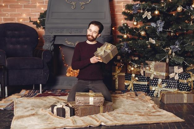 赤いセーターで幸せな男。暖炉の前の男。クリスマスツリーの背景に男性。