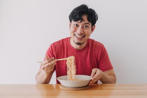 Счастливый человек в красной футболке ест лапшу быстрого приготовления на белом фоне