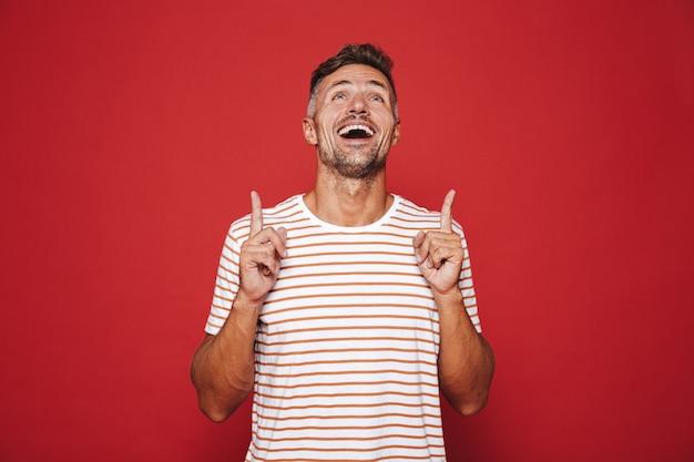 Счастливый человек в полосатой футболке показывает указательными пальцами вверх на copyspace, изолированном на красном