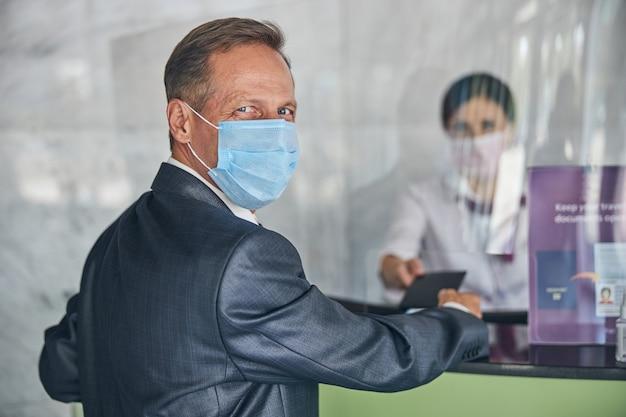 정장을 입은 행복한 남자가 마스크를 쓰고 등록 데스크에서 여성에게 문서를 주고 있다