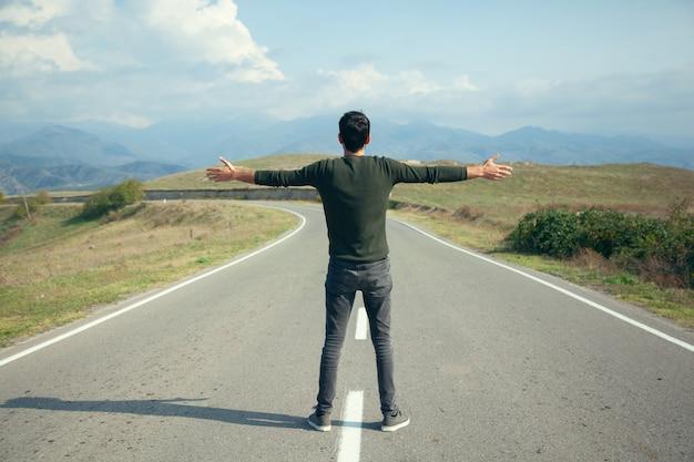 空のアスファルト道路で幸せな男