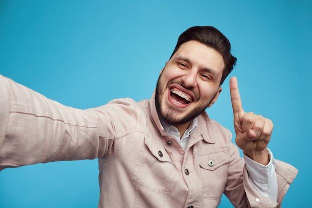 Счастливый человек в модном наряде улыбается и показывает вверх, делая селфи