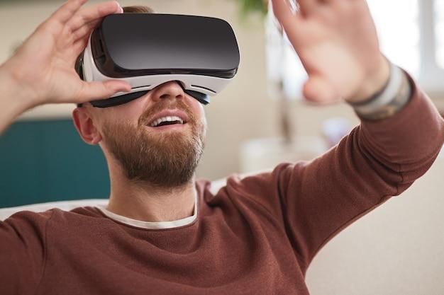Счастливый человек в гарнитуре vr, взаимодействующий с виртуальным миром