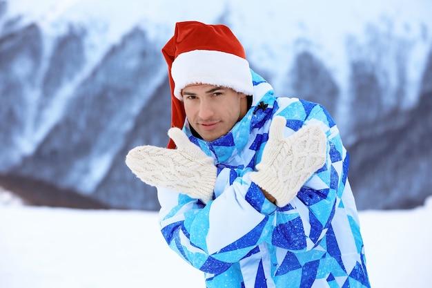 屋外で楽しんでいる暖かいミトンの幸せな男。冬休み