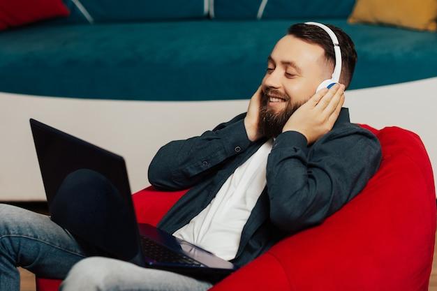 自宅の赤い肘掛け椅子でリラックスしたラップトップとワイヤレスヘッドフォンで幸せな男。