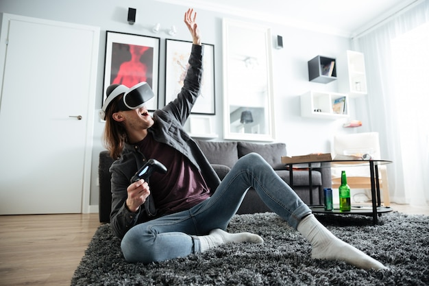 Happy man indoors play games with 3d virtual reality glasses