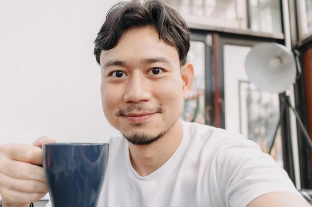 幸せな男がカフェで温かい飲み物のコーヒーを飲んでいる