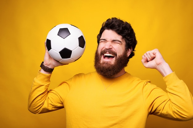 Happy man is makes winner gesture while holding a football or soccer ball.