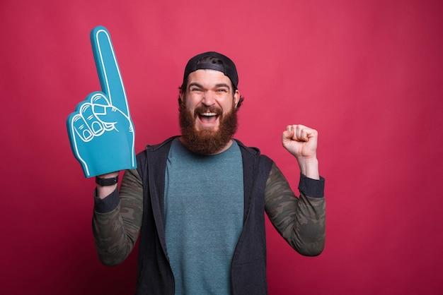 Счастливый человек делает жест победителя с перчаткой вентилятора пены