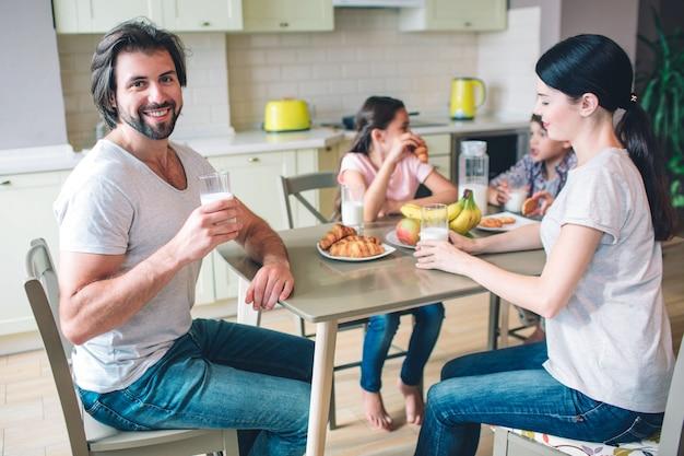 행복한 사람이 그의 가족과 함께 테이블에 앉아있다. 그는 우유를 마신다. 가족의 다른 구성원은 음식을 먹고 서로 이야기하고 있습니다.